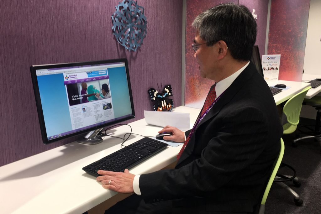 Dr. Ching Lau at a computer. (Lauren Woods/UConn Health Photo)