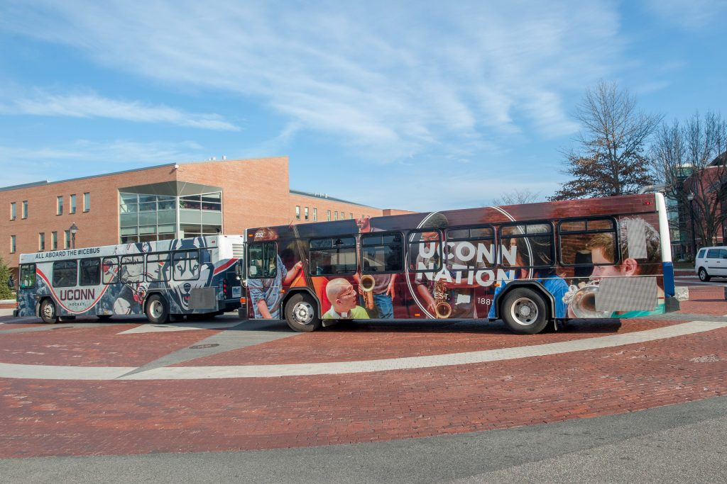 A UConn Nation transportation bus, right, and the Icebus, on Hillside Road. (Sean Flynn/UConn Photo)
