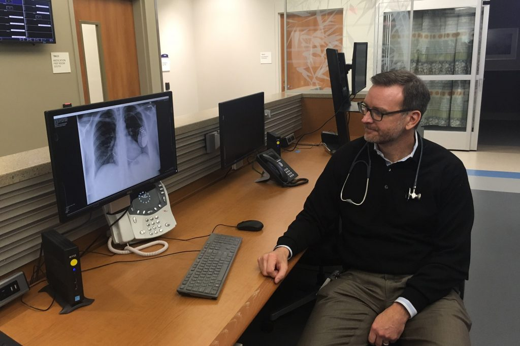Electrophysiologist Dr. Christopher Pickett at UConn Health's Calhoun Cardiology Center is continuing to monitor Vanessa Lloyd's heart remotely, using a device implanted under her skin.