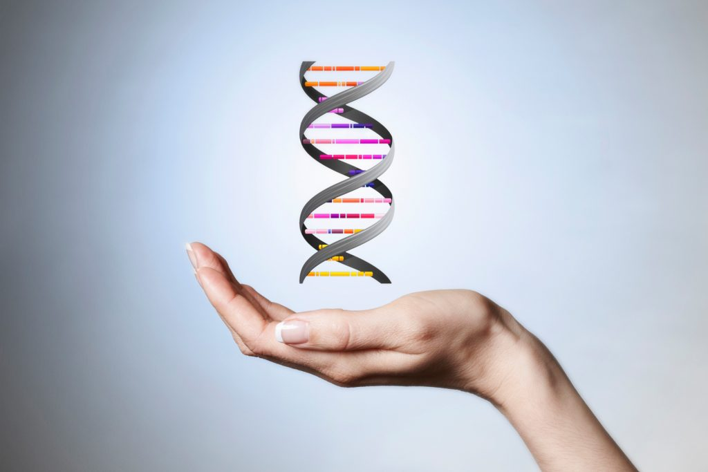 Hand holding strand of DNA. (Getty Images)