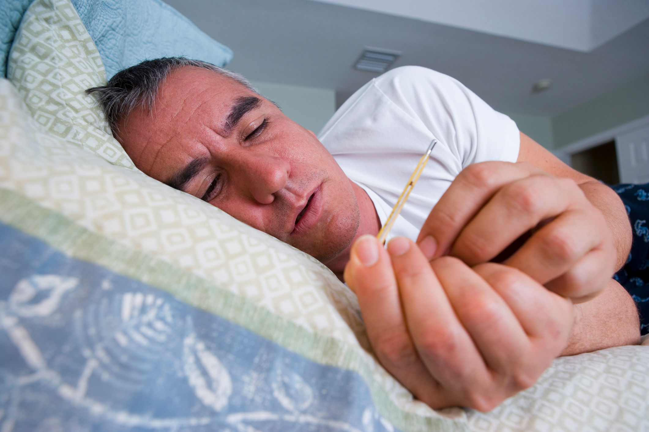 Sick man in bed holding thermometer. (Juan Silva via Getty Images)
