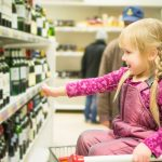 The alcohol industry still makes ads appealing to youth. Girl in shopping cart image via www.shutterstock.com.
