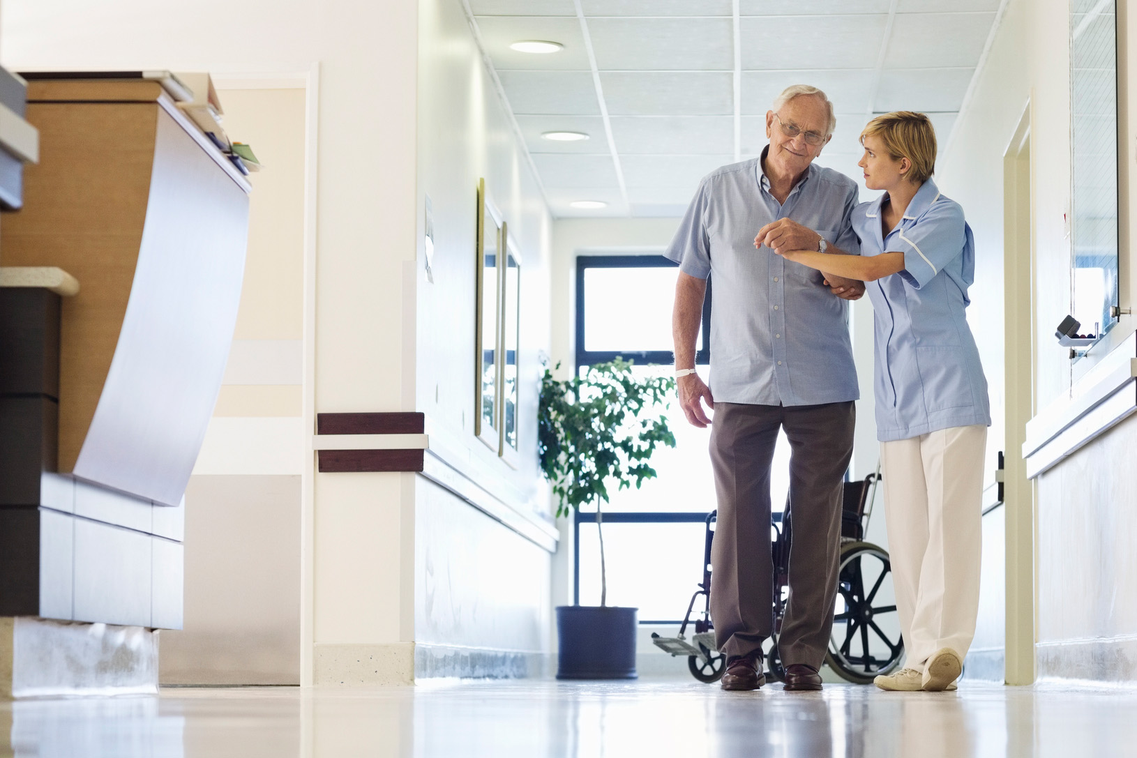 A senior patient begins to walk a hospital hallway with help from a nurse. (Getty Images)