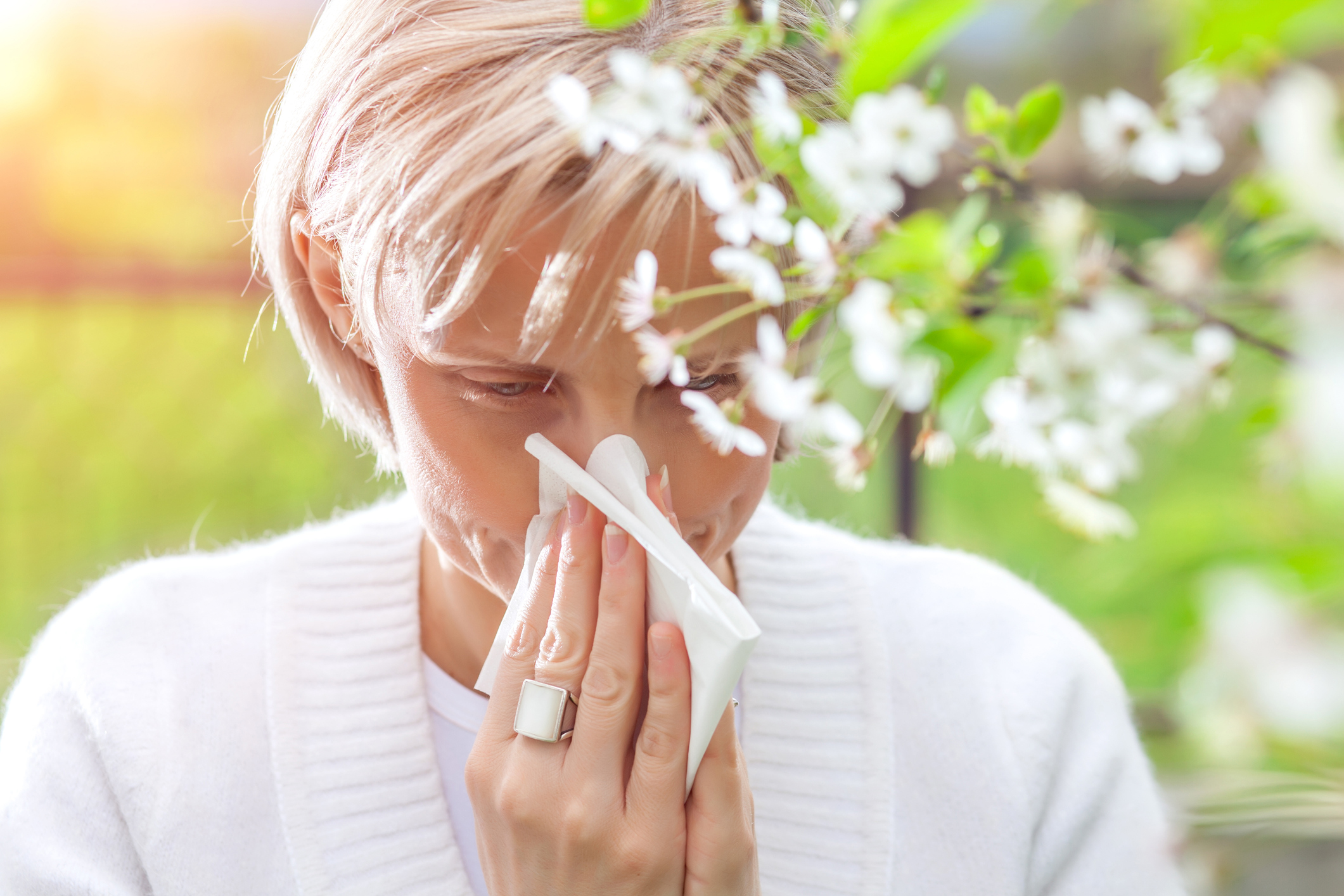 Woman sneezing, standing next to a tree in bloom. (Getty Images)