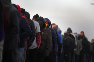 Migrants queue to board buses and leave the notorious 'Jungle' camp in Calais, France, before authorities demolished the site in fall 2016 in Calais, France. Some 7,000 people were estimated to be living in the camp in squalid conditions. (Christopher Furlong/Getty Images)