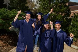 From left, Christopher Chapman '17 (CLAS), Isabel Nip '17 (CLAS), Danielle Deschene '17 (CLAS), and Shaharyar Zuberi '17 (CLAS) wear the new blue commencement caps and gowns while posing next to the Husky statue. (Peter Morenus/UConn Photo)