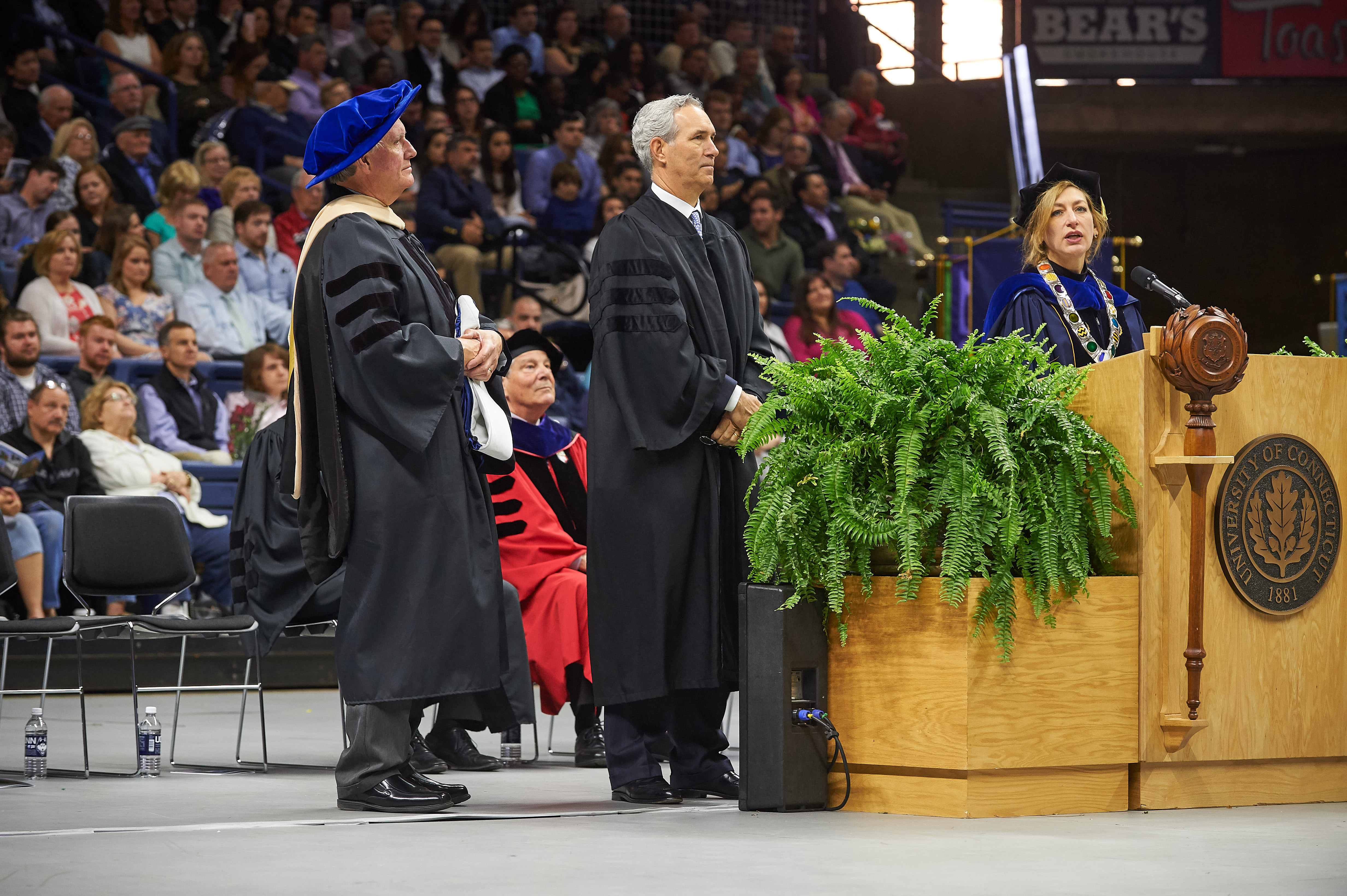 Douglas Elliot '82 (BUS), center, listens as President Susan Herbst, right, reads the citation and Lawrence Gramling, associate dean, holds a hood as Elliot receives an honorary degree during the School of Business Commencement ceremony at Gampel Pavilion on May 7, 2017. (Peter Morenus/UConn Photo)
