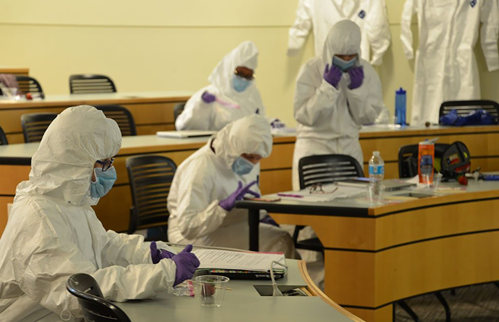 """Participants in a """"CSI Forensics in the Classroom"""" Confratute session suit up for a lesson on testing for DNA evidence this July in Storrs. (Photo Credit: Shawn Kornegay/Neag School)"""