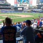 A participant in the River House Baseball Reminiscence Program and her son cheer on the Mets at Citi Field. (Kenneth Best/UConn Photo)