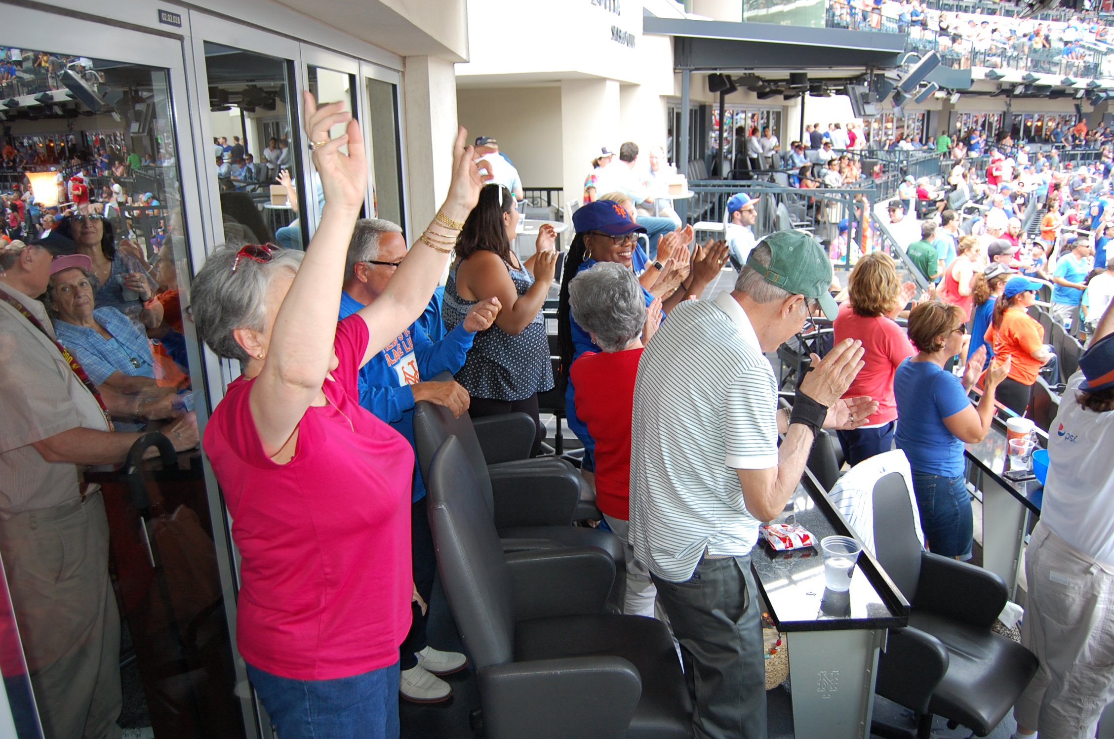Participants and staff from the River House Adult Care Center in Cos Cobb, Connecticut, cheering on the New York Mets at Citi Field in New York City, as part of the Baseball Reminiscence Program. (Kenneth Best/UConn Photo)