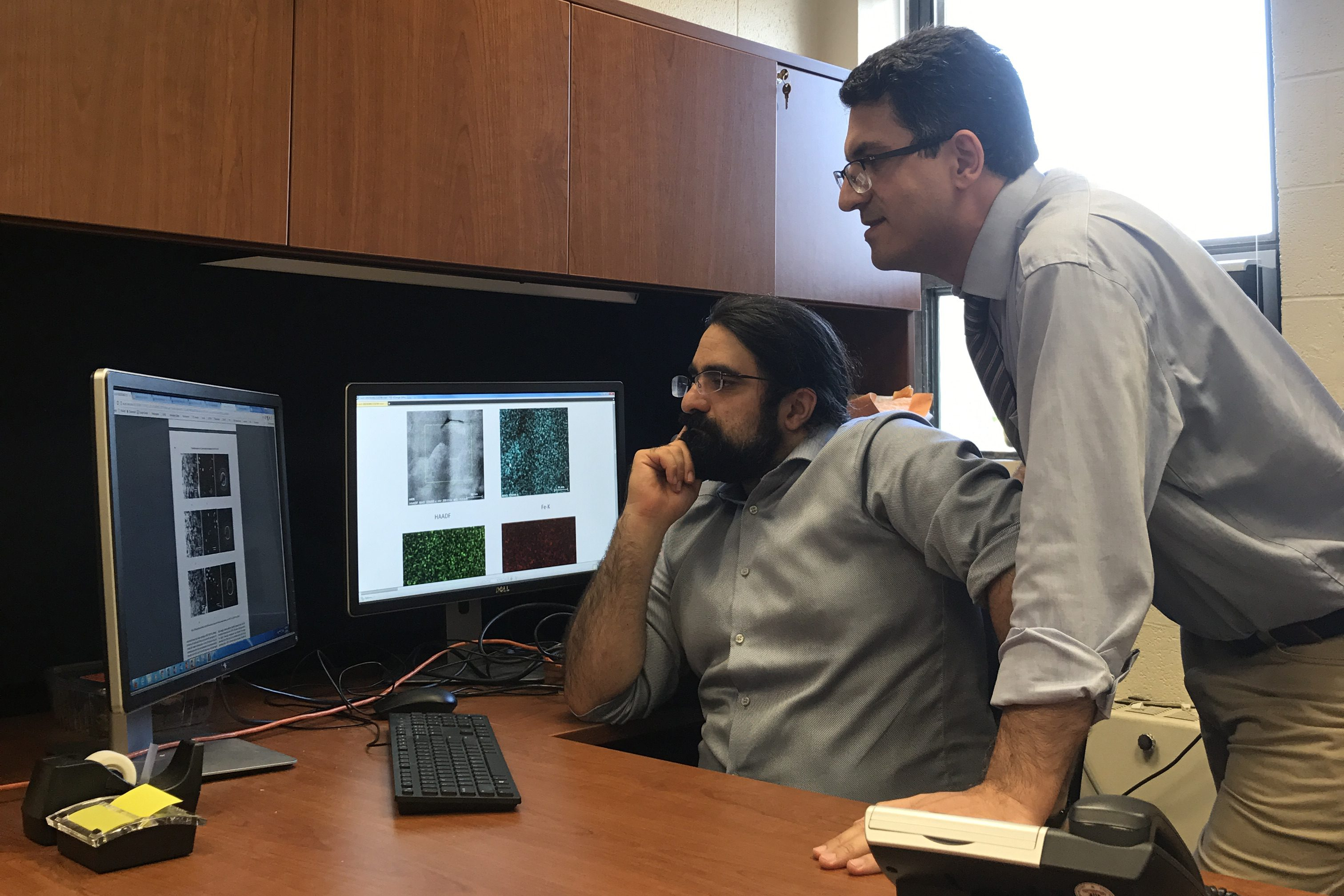 Postdoctoral researcher Peiman Shahbeigi (standing) and Sina Shahbazmohmadi, assistant professor in biomaterials engineering, discuss grain microstructures characterized by an advanced electron microscope.
