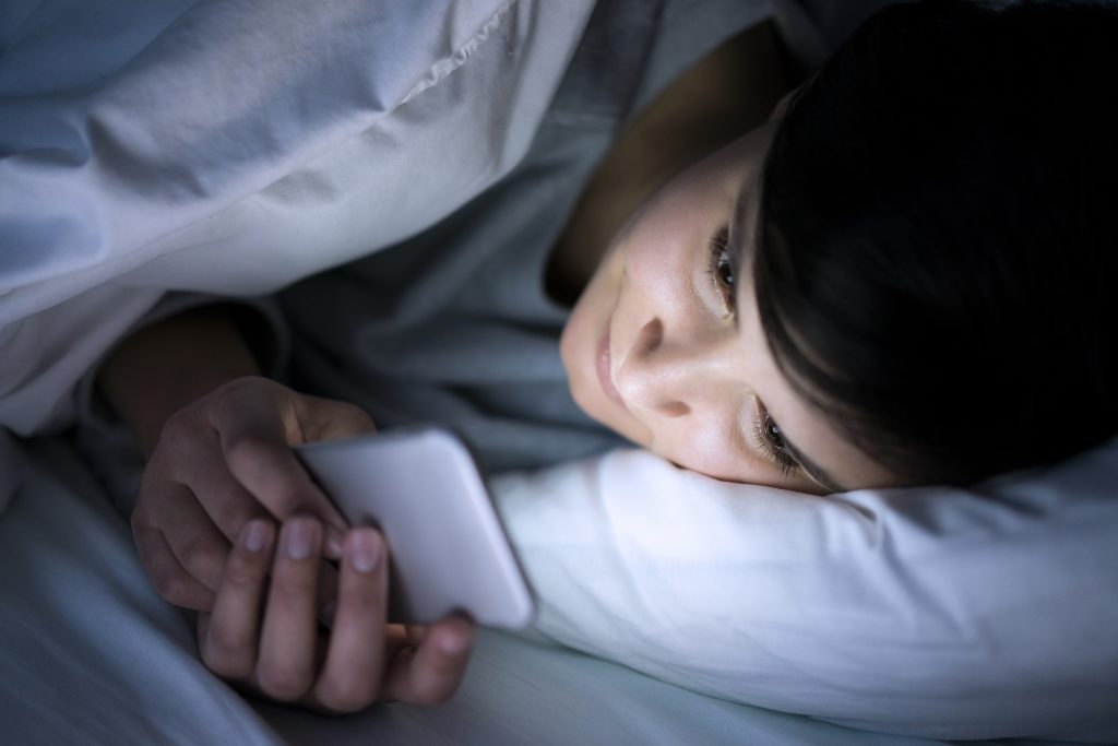 Woman using her phone under blanket in bed at night. (Getty Images)
