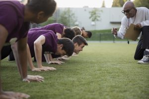 Physical education teacher encouraging students doing push-ups. (Hero Images via Getty Images)