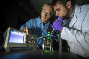 Associate professor of mechanical engineering George Lykotrafitis, left, and Ph.D. student Kostyantyn Partola demonstrate their whole blood rheometer technology. (Sean Flynn/UConn Photo)