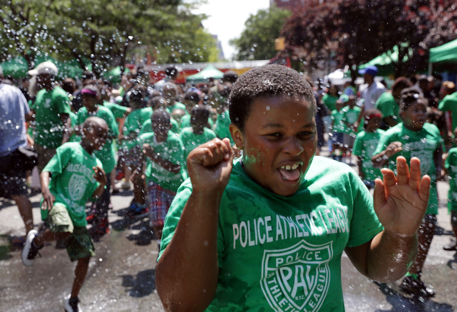 Children run through an open fire hydrant to cool off during the kickoff of the 2016 Summer Playstreets Program in the Harlem neighborhood of New York, July, 6, 2016. (AP Photo/Ezra Kaplan via The Conversation)
