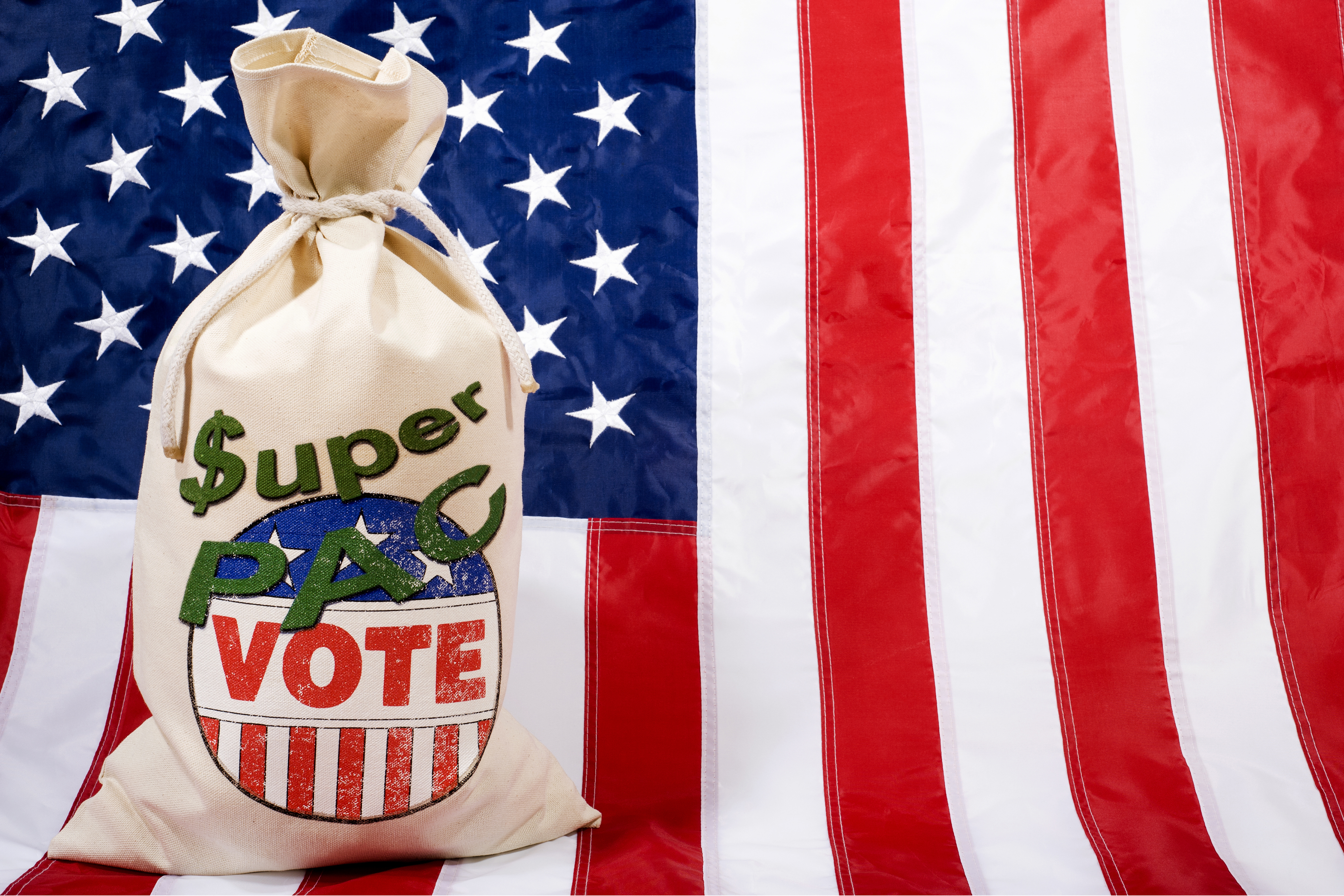 Money bag against a U.S. flag as background. Concept of the Super PACs' influence on the Presidential elections in the United States. (Getty Images)