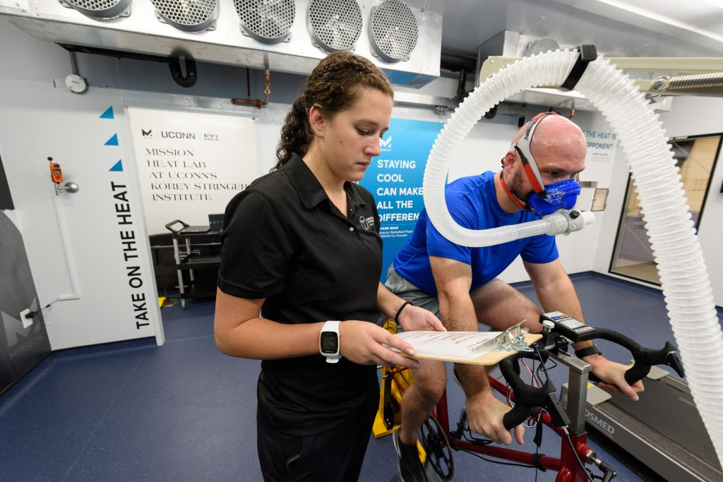 Gabrielle Giersch, a Ph.D. student and KSI assistant director of athlete performance and safety, looks on while Ryan Curtis, a Ph.D. student and KSI associate director of athlete performance and safety, rides an exercise bicycle at the Mission Heat Lab at the Korey Stringer Institute at Gampel Pavilion on Sept. 21, 2017. (Peter Morenus/UConn Photo)