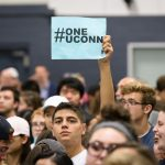 A student holds a #OneUConn sign during the rally. Speaker after speaker warned of the risks to financial aid, academic life, the University's ability to serve as an economic growth engine for Connecticut, and the national reputation that UConn has won for itself and its state. (Peter Morenus/UConn Photo)