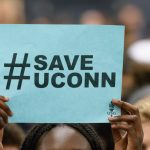 A student holds up a #SaveUConn sign during a rally at the Hugh S. Greer Field House in support of the University on Sept. 20, 2017. (Peter Morenus/UConn Photo)