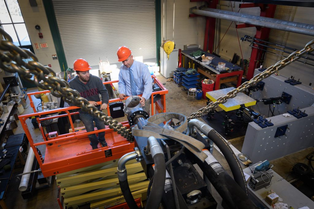 Richard Christenson,professor of civil and environmental engineering, right, and Michael Harris '10 (ENG) '13 MENG, a Ph.D. student, attach a mounting ring to a hydraulic ram in the lab at the Castelman Building on Oct. 19, 2017. (Peter Morenus/UConn Photo)