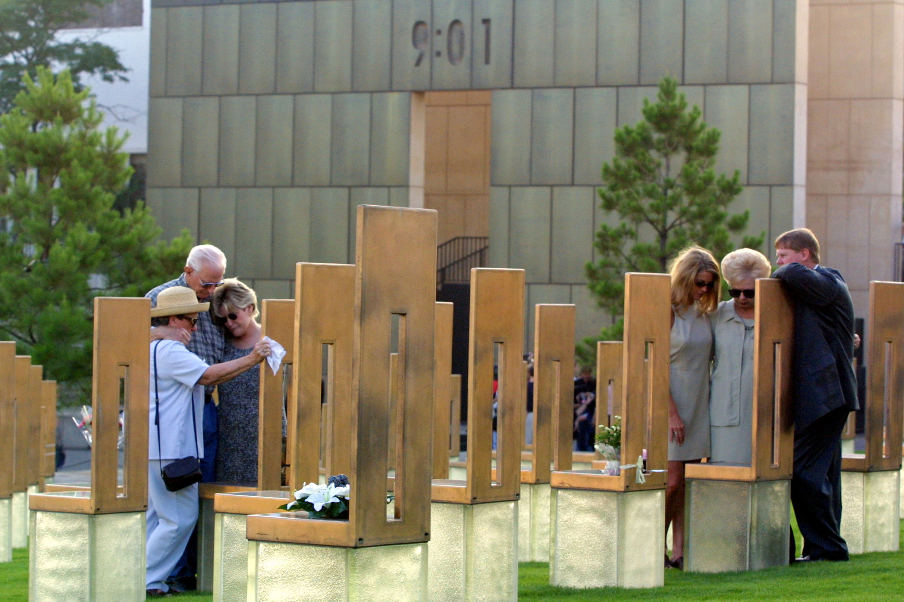 Mourners gather at the Oklahoma City National Memorial around chairs representing relatives killed during the 1995 bombing, on the day perpetrator Timothy McVeigh was executed, June 11, 2001. On the wall behind them, the time when the bomb was detonated is recorded at 9:01. (Joe Raedle/Getty Images)