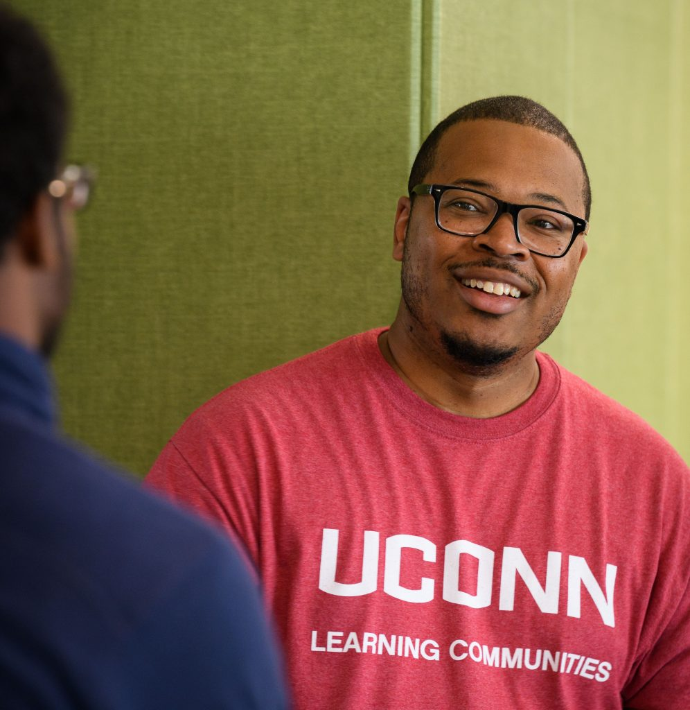 Erik Hines, assistant professor of educational psychology and director of ScHOLA²RS House, speaks with a student. (Peter Morenus/UConn Photo)