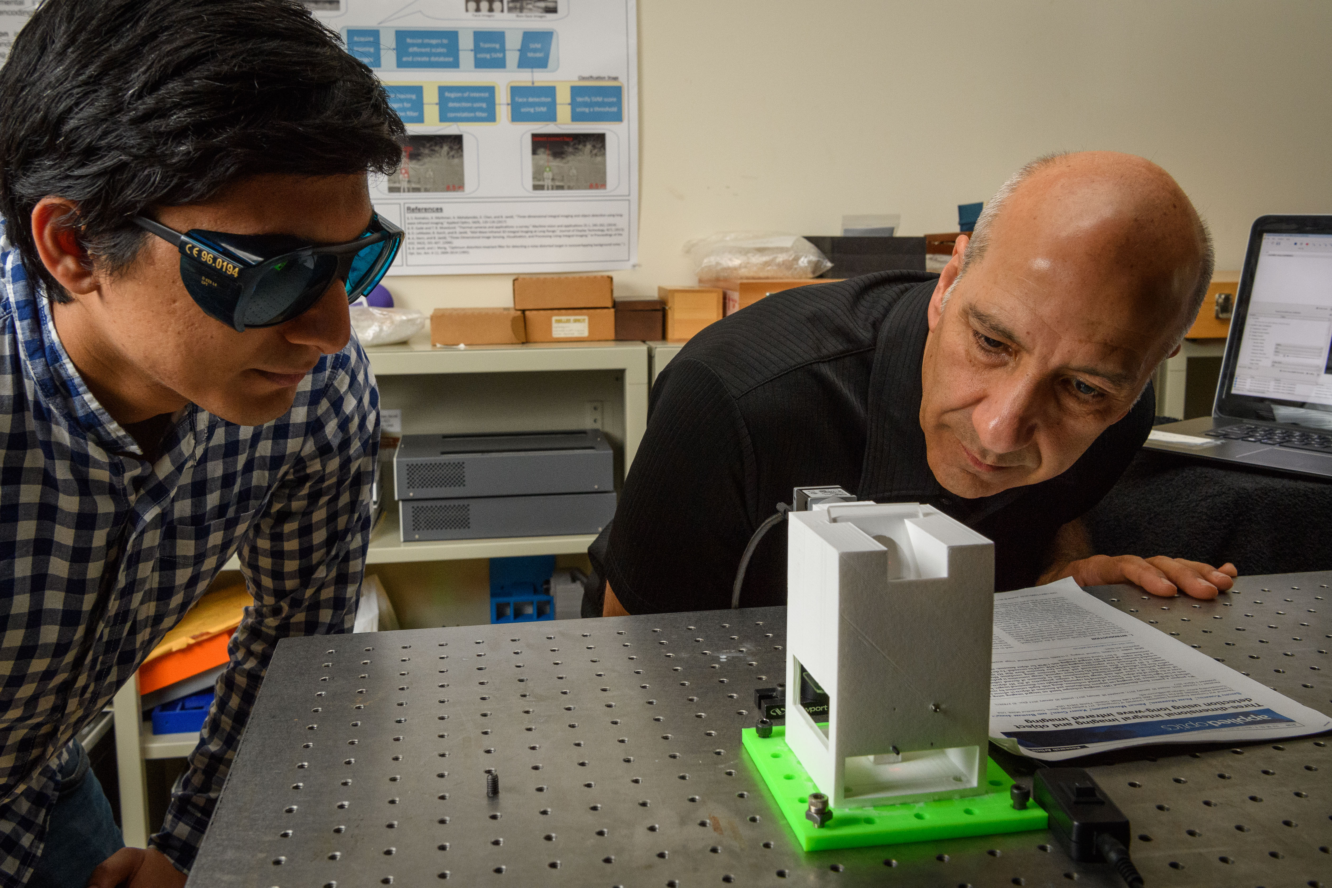 Siddharth Rawat, left, a Ph.D. student, and Bahram Javidi, distinguished professor of electrical and computer engineering, operate a prototype device to examine blood samples for diseases at the Information Technologies Engineering Building (ITE) on Sept. 28, 2017. (Peter Morenus/UConn Photo)