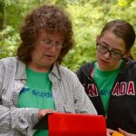 Laurie Doss, left, of Kent Land Trust and Marvelwood School, and Lillian Steinmayer of Marvelwood School, practice using geospatial technology in the UConn Forest. The activity was part of the NRCA's Conservation Training Partnerships program, in which teams of teens and adults take part in a two-day conservation workshop and project. (NRCA Staff/UConn Photo)
