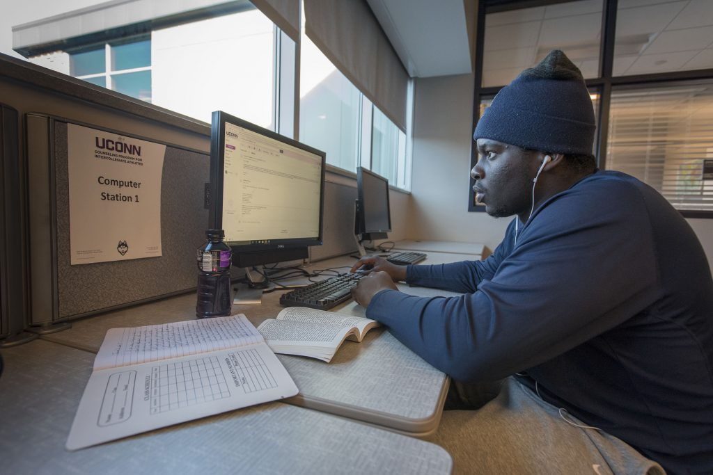 Student-athlete Foluronso 'Foley' Fatukasi, Football , writing a paper in the study lounge of the Burton Football Complex. (Sean Flynn/UConn Photo)