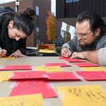 Lauren Graham '18 (CLAS), left, and Zachary Corolla '18 (CLAS) write their ideas on combating racism onto paper leaves at a table hosted by the USG Student Development Committee during a Metanoia event titled 'Leaf A Mark.' (Peter Morenus/UConn Photo)