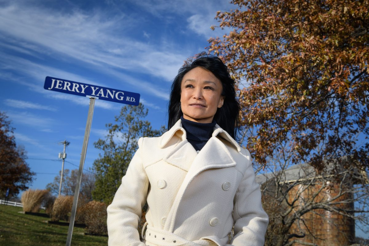 Xiuchun 'Cindy' Tian stands next to a roadsign bearing the name of her late husband, UConn researcher Jerry Yang, who is known for his pioneering work in animal cloning. (Peter Morenus/UConn Photo)
