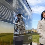 Animal science professor Cindy Tian stands next to a sign depicting Jerry Yang and agricultural research at UConn. (Peter Morenus/UConn Photo)