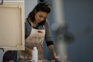 Marissa Aldieri '18, an individualized major, works on her painting in Professor Guarino's Basic Painting class. (Garrett Spahn/UConn Photo)