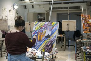 Katie Ouimette, a junior majoring in fine arts, works on her painting in Professor Guarino's class. (Garrett Spahn/UConn Photo)
