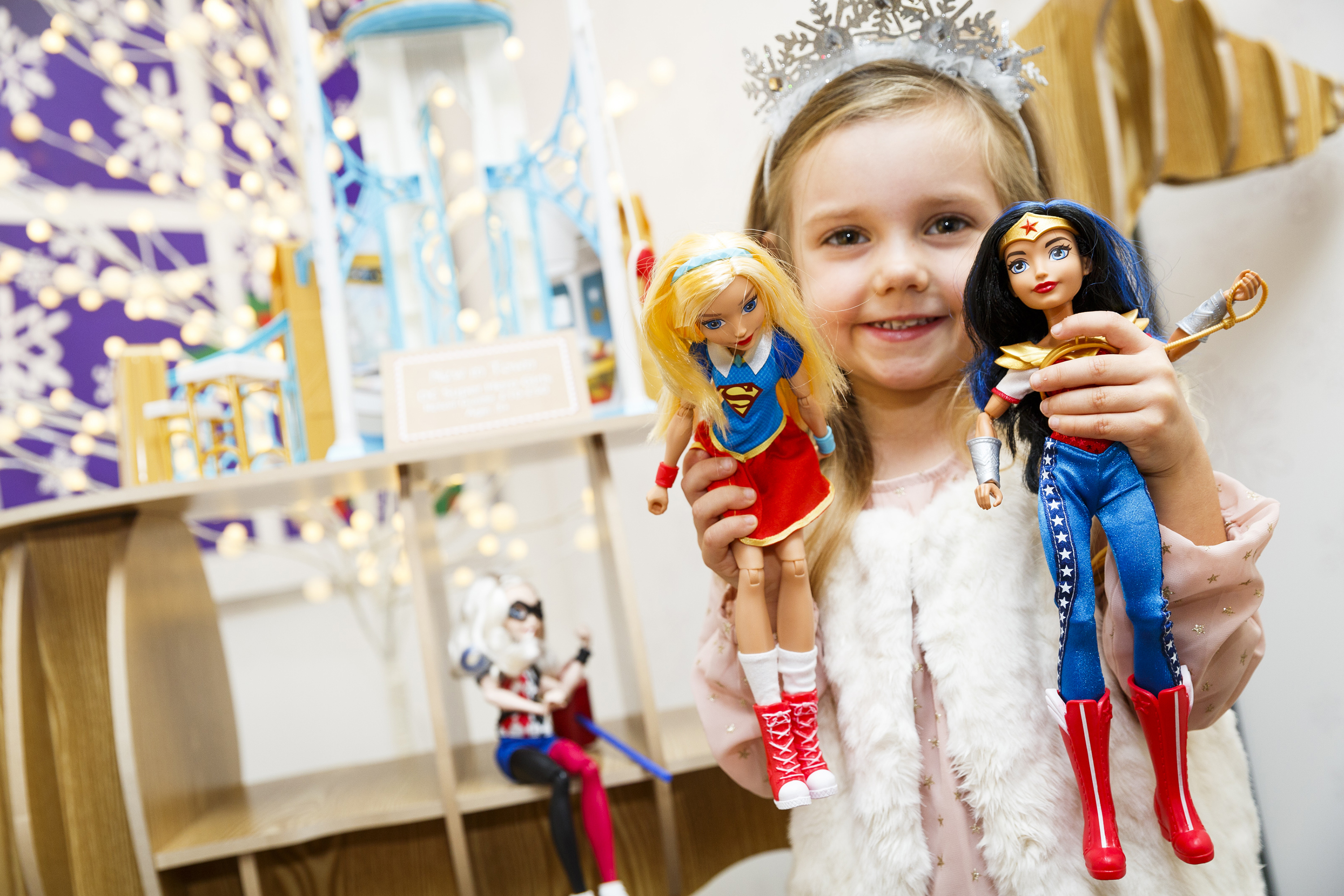 A little girl holds up Supergirl, left, and Wonder Woman, two characters from Mattel's DC Super Hero Girls collection. The appearance and dress of the new generation of fashion doll characters is a departure from Barbie's idealized image and has changed the way children play, according to graduate student Sara Austin. (Tristan Fewings/Getty Images)