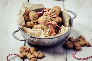 Gingerbread man cookies and Christmas decorations on white background. (Getty Images)