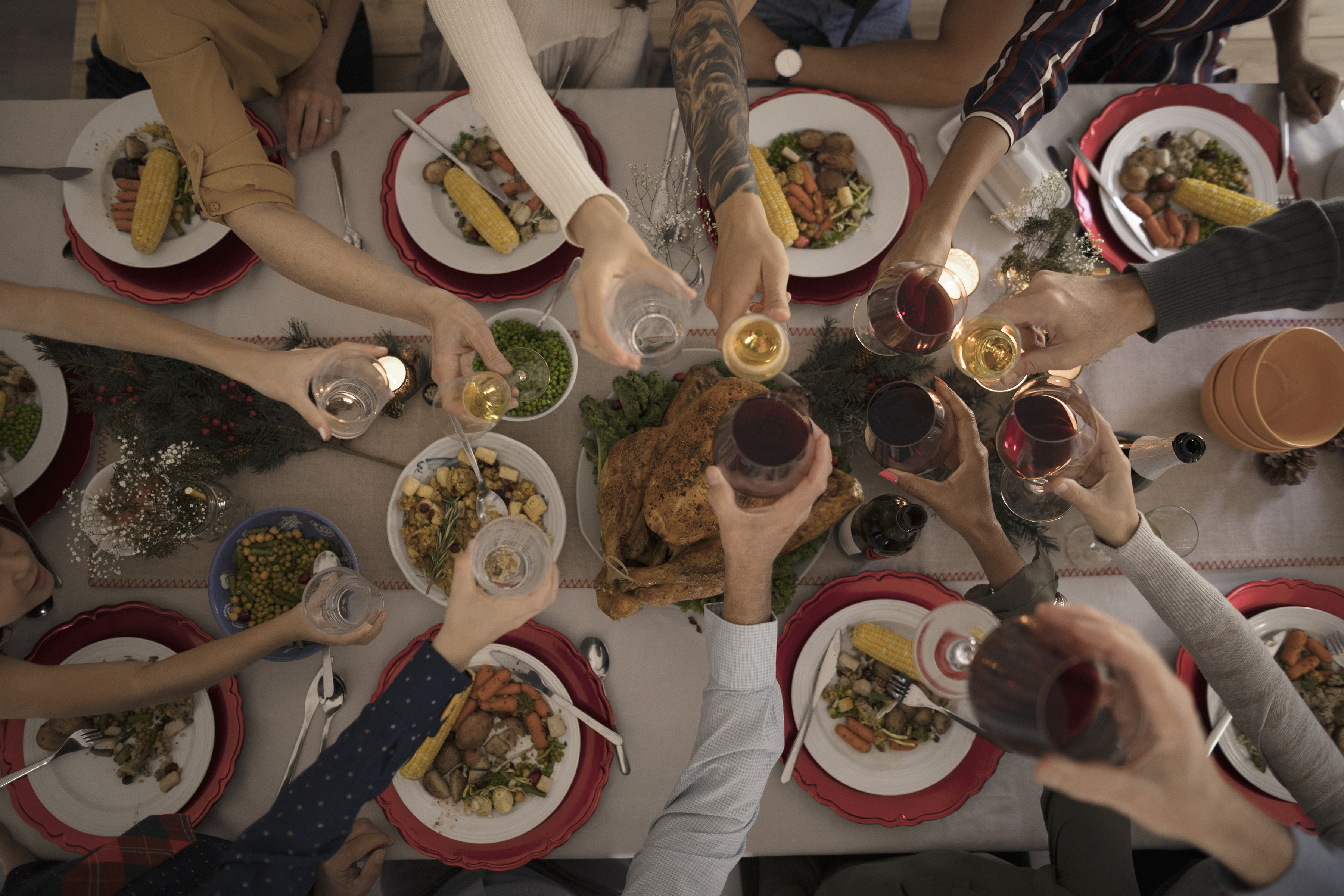 Overhead view family toasting wine glasses at candlelight Christmas turkey dinner at table. (Hero Images/Getty Images)