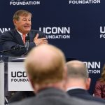 Peter J. Werth speaks at an event to announce his $22.5 million commitment to the University and the naming of the Peter J. Werth Residence Tower. Seated is President Susan Herbst. (Peter Morenus/UConn Photo)