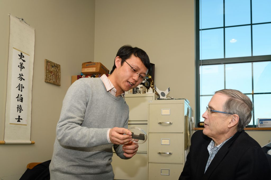 Steven Suib, Board of Trustees Distinguished Professor of Chemistry, right, with Junkai He, a Ph.D. candidate, at his office in the Chemistry Building. (Peter Morenus/UConn Photo)