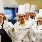 Michelle Perez of Buckley dining, and other competitors walk into Rome Ballroom at the start of the Boiling Point competition of UConn Dining's 18th annual Culinary Competition on Jan. 9, 2018. (Peter Morenus/UConn Photo)