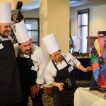 Gary Ellis, left, Scott Chapman, and Susan Chang, all of McMahon dining, watch as they spin a wheel to select an additional ingredient for their entry during the Boiling Point competition. (Peter Morenus/UConn Photo)