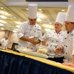 Mathew Nichols, left, Hannah Lee, and Bill McKay look over their ingredients at the start of the Boiling Point competition. (Peter Morenus/UConn Photo)
