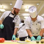 Ryan Shepard, left, looks on as Ivan Rojas, both of Buckley dining, prepares potato skins. (Peter Morenus/UConn Photo)