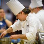 Matthew Nichols of Putnam dining puts potato gnocchi into a pot. (Peter Morenus/UConn Photo)