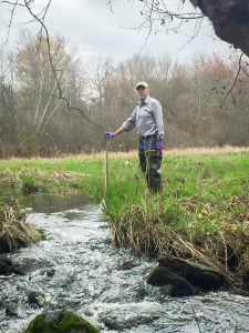 Professor John Clausen installing a stage sampler water collector device in the Conantville Brook. (Submitted)