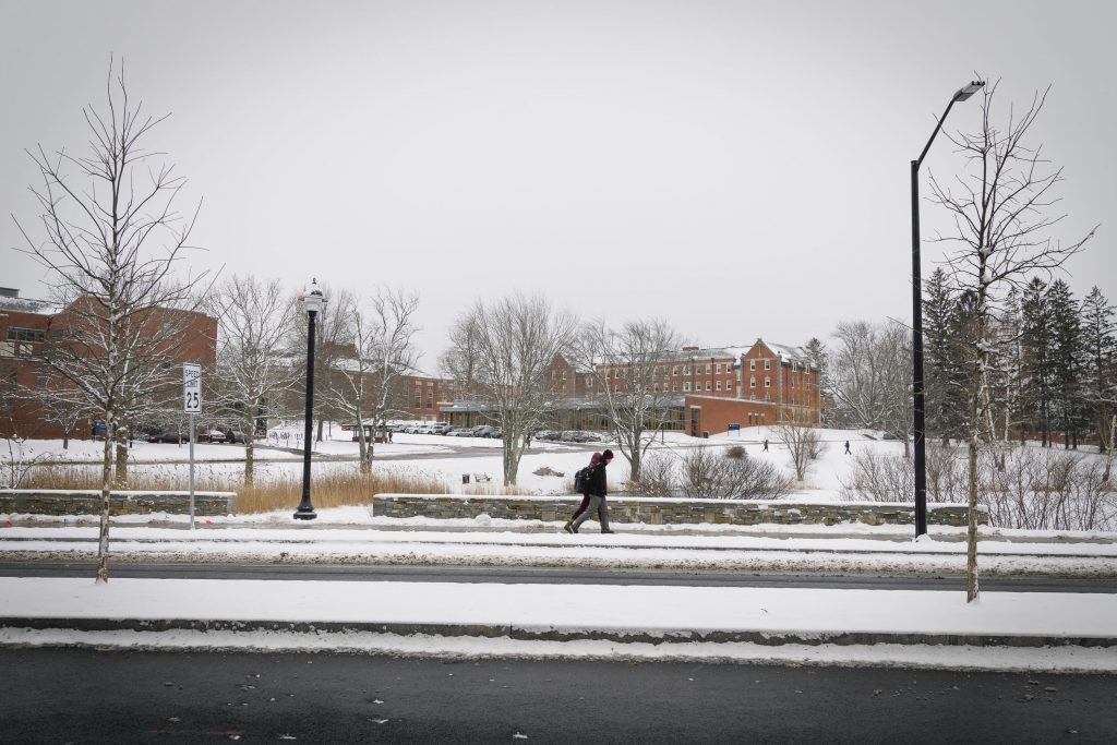 A view of North Eagleville Road in the snow, showing renovations including a new median, expanded sidewalk, stone wall, and new lighting. (Peter Morenus/UConn Photo)