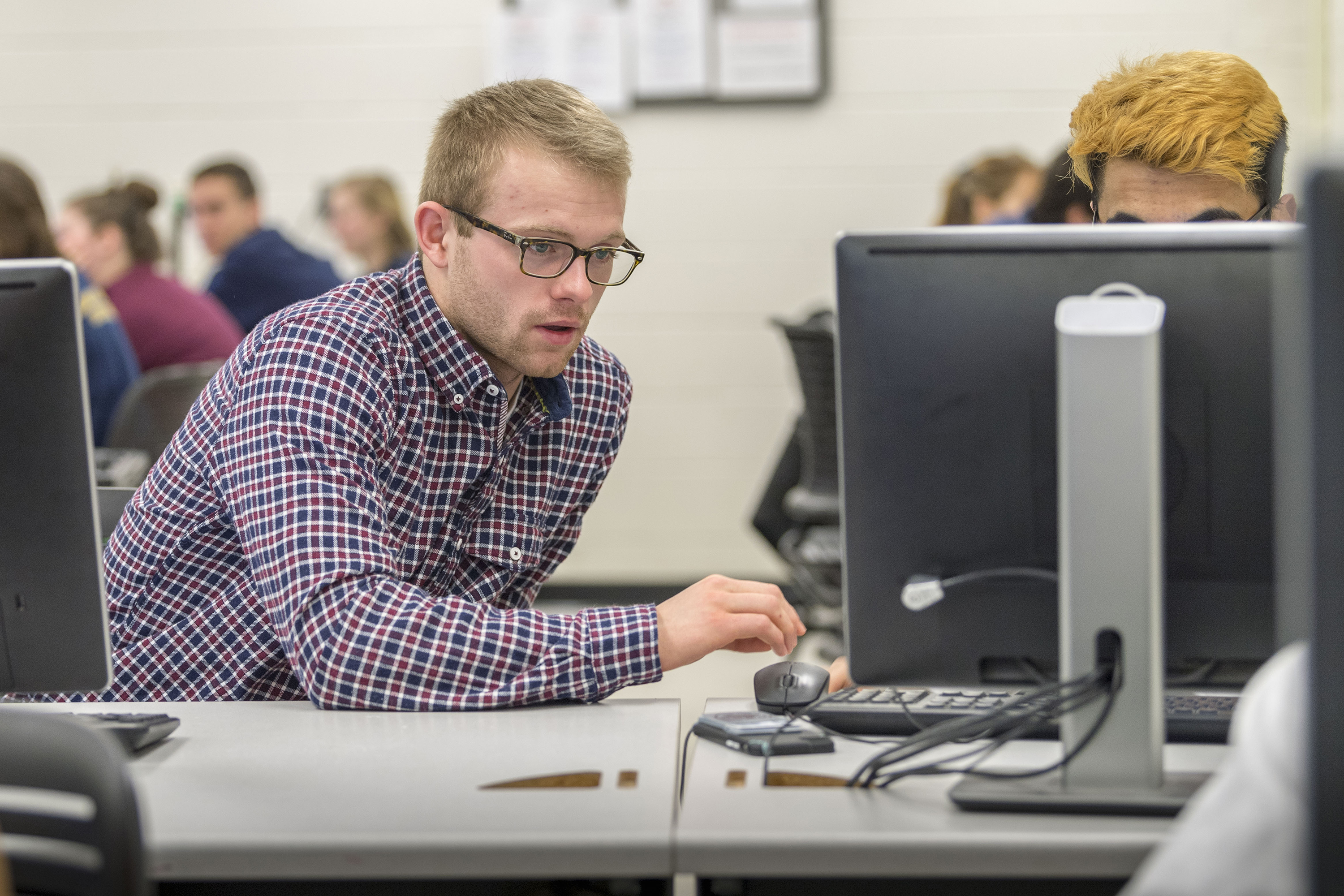 (left) Men's swimming student athlete: Matt Dagenais '19 (ENG) in his Computer Aided Design class at the School of Engineering's Castleman Building on Feb. 20, 2018. (Sean Flynn/UConn Photo)