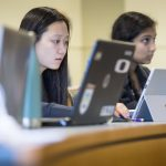 Student-athlete Julie Hu '19 (CLAS) listening to a finance lecture by assistant professor Cristian Pinto-Gutierre in the School of Business on Feb. 21, 2018. (Sean Flynn/UConn Photo)