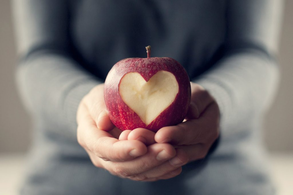 An apple with a heart-shape carved out of it. (Getty Images)