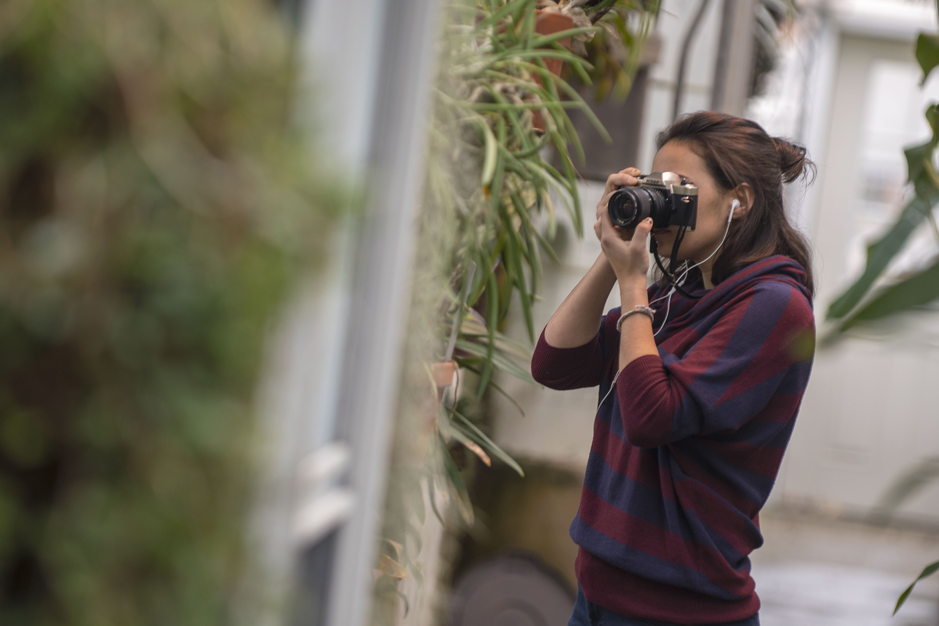 Marissa Aldieri '18 (CLAS), an individualized major, takes photos for Intermediate Photography taught by Kaleigh Rusgrove at the UConn Biodiversity Education and Research Greenhouses on Feb. 12, 2018. (Garrett Spahn '18 (CLAS)/UConn Photo)